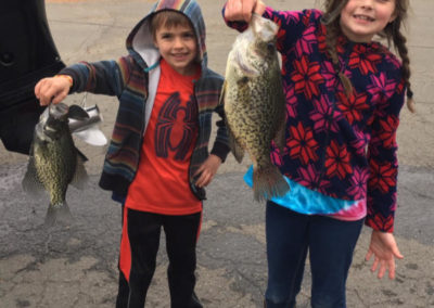 children holding fish caught from lake maumelle